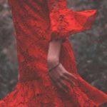 Een zwierige rode jurk. De vrouw die hem draagt doet zich voor als opgewekt en blij. Je ziet alleen de jurk, niet haar gezicht. Een vrolijke kleur tegen een donkere achtergrond.