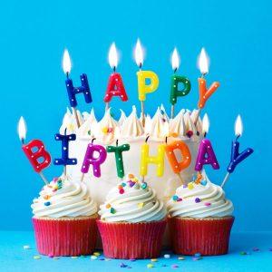 Verjaardagstaart met cup cakes kaarsjes in de vorm van de letters Happy Birthday.