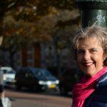 Een vrouw staat met haar gezicht half in de zon op een gracht in Den Haag. Zij straalt vertrouwen uit.
