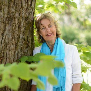 Een vrouw staat in de vroege lente naast een boom. Ze draagt een witte blouse en een turquoise sjaal en haar zonnebril staat op haar hoofd. Op de voorgrond het zachte groen van voorjaarsbladeren.