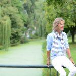 Een vrouw zit op een hek bij het water en is zichtbaar gelukkig met haar leven