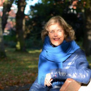 Een vrouw zit op een bankje in het park. Het lage licht in de herfst tovert schaduwen op haar gezicht.