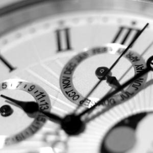 Op de foto staat een deel van een klok. De klok heeft Romeinse cijfers en een datumaanduiding. Hij doet klassiek aan.