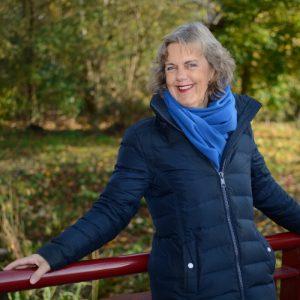 Een vrouw staat op de brug. Ze leunt met haar rug tegen de leuning en haar hand ligt er losjes bovenop. Zij draagt een blauwe jas en een felblauwe sjaal