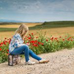 Een vrouw zit aan de kant van de weg op haar koffer. Het beeld laat zien dat zij de bagage van haar verleden met zich meeneemt, en vandaaruit een nieuwe weg inslaat. Op de achtergrond rode klaprozen als teken van hoop.