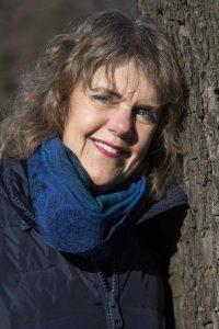 Een vrouw staand met haar hoofd geleund tegen een boom. Ze draagt een blauwe sjaal en een blauwe jas. De winterzon schijnt in haar gezicht.