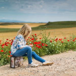 Een vrouw zit op haar koffer aan de kant van de weg. Achter haar een veld met rode klaprozen. Ze neemt haar verleden mee, maar is een nieuwe weg ingeslagen. Het rood van de klaprozen is het teken van hoop.