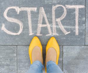 Op de stoep staat met krijt het woord start geschreven. Een dame met Jeans en gele pumps is klaar voor de start. Je ziet nog een deel van haar benen en haar voeten, waarvan de punten van haar schoenen na het woord start wijzen.