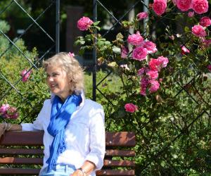 Een vrouw zit op een bankje met achter zich een rek met klimrozen. De zon schijnt. Zij draagt een lichte blouse en een felblauwe sjaal. De roos en zijn fel roze. Zij glimlacht vaag.