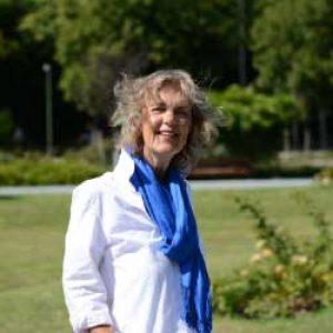 Een vrouw staat in het park. Zij draagt een lichte blouse en een felblauwe sjaal. Zij kijkt vrolijk en geniet van het mooie weer. Haar haar waait omhoog door een windvlaag.