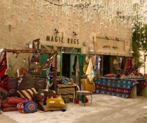 Een winkel met handgemaakte tapijten in Dubai. Voor de winkel liggen talloze kleurige tapijten en kussens. De winkel draagt de naam Magic Rugs, magische tapijten en. De foto ademt een Oosterse sfeer.