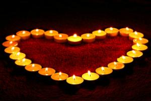 Op een rood tapijt staan brandende waxinelichtjesIn de vorm van een hart