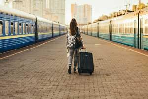 Een vrouw met een rolkoffer loopt op een verlaten perron. Aan weerszijden staan treinen. In de verte zijn hoge gebouwen zichtbaar.
