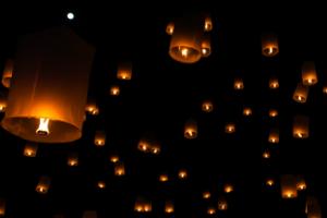 Tegen een donkere lucht, zie je een aantal Chinese wensballonnen, die zijn opgelaten.