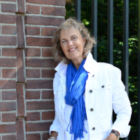 Er staat een verhaal met een wit jasje en felblauwe sjaal geleund tegen een muur en een hek. Ze kijkt in de verte en glimlacht. De wind waait haar haar naar voren.