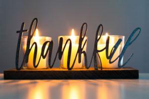 drie kaarsjes branden. Met zwierige letters staat er Thankful over heen geschreven.