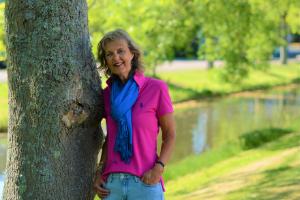 Een vrouw staat geleund tegen een dikke boom. Het is voorjaar. Zij draagt een lichtblauwe jeans en een felroze poloshirt met een hardblauwe sjaal, Haar handen losjes in de zakken. Zij heeft halflang donker haar met hier en daar grijze strepen.met h