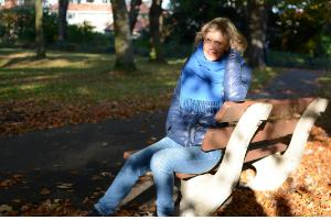 Een vrouw zit op een bankje in het bos. Ze draagt een blauwe sjaal en heeft halflang donkerblond haar. De zon tovert lichtvlekken op haar gezicht.