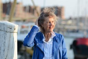 Een vrouw staat aan de haven. Haar haar waait omhoog en zij houdt het in bedwang met haar rechterhand. Zij draagt een felblauw jasje en een blauw wit gestreepte blouse. Zij kijkt in de verte en glimlacht.