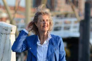 Een vrouw staat aan de haven. Haar halflange donkere haar waait omhoog.Zij houdt het tegen met haar hand. Ze is van middelbare leeftijd en draagt een kobaltblauw jasje en gestreepte blouse. Ze kijkt in de verte en lacht.